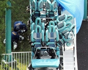 Police officers investigate the site of a roller coaster accident in Suita, western Japan, Saturday, May 5, 2007. A roller coaster traveling up to 75 kilometers (46 miles) per hour hit a guardrail at an amusement park in western Japan on Saturday, killing one person and injuring 21 others, officials said. (AP Photo/Kyodo News) ** JAPAN OUT, NO SALES, MANDATORY CREDIT